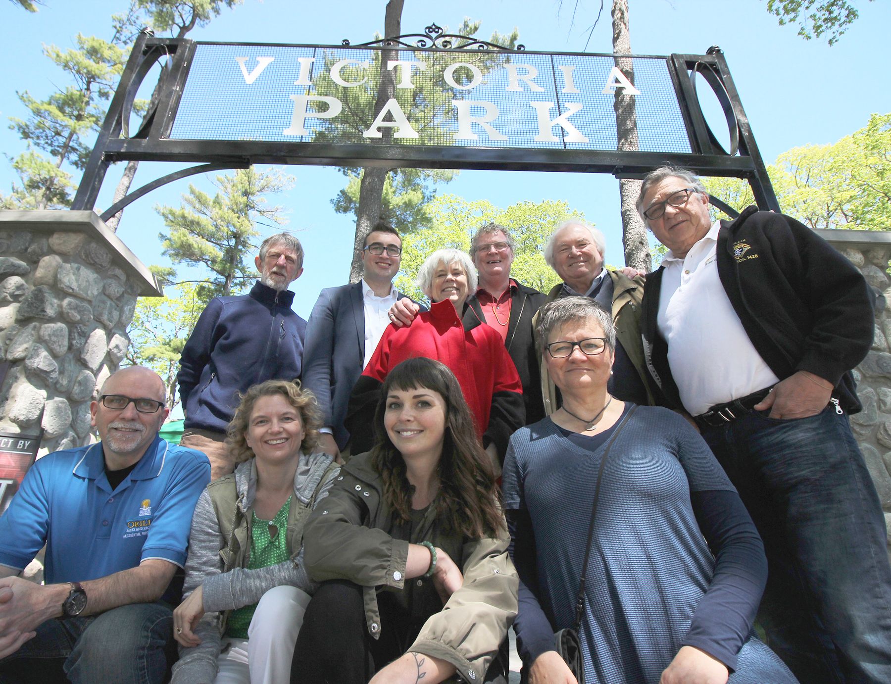 From top left – Coun. Tim Lauer, Coun. Mason Ainsworth, Coun. Pat Hehn, Mayor Steve Clarke, Coun. Ted Emond, Coun. Ralph Cipolla, Ray Merkley, Jacqueline Soczka and Haleigh Fox from Parks, Recreation and Culture and Sylvie Browne, granddaughter of Elizabeth Wyn Wood, gather to celebrate the new feature entryway sign at Victoria Park during Art Park on May 20, 2017.