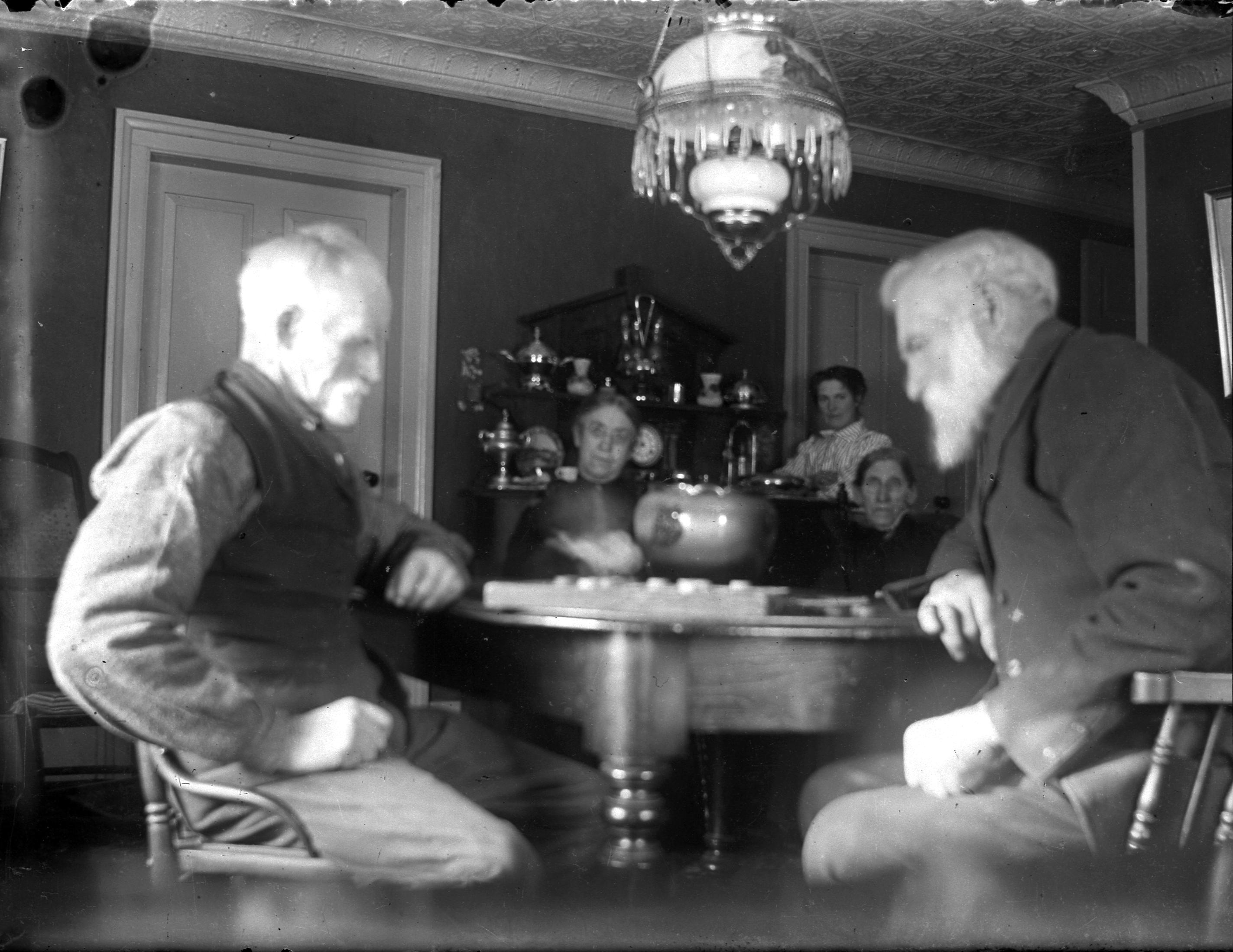 Peter McLeod and friend John MacDonald playing checkers, 1890