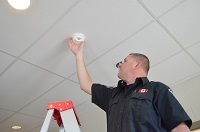 Fire Prevention Inspector Installing Smoke Alarm