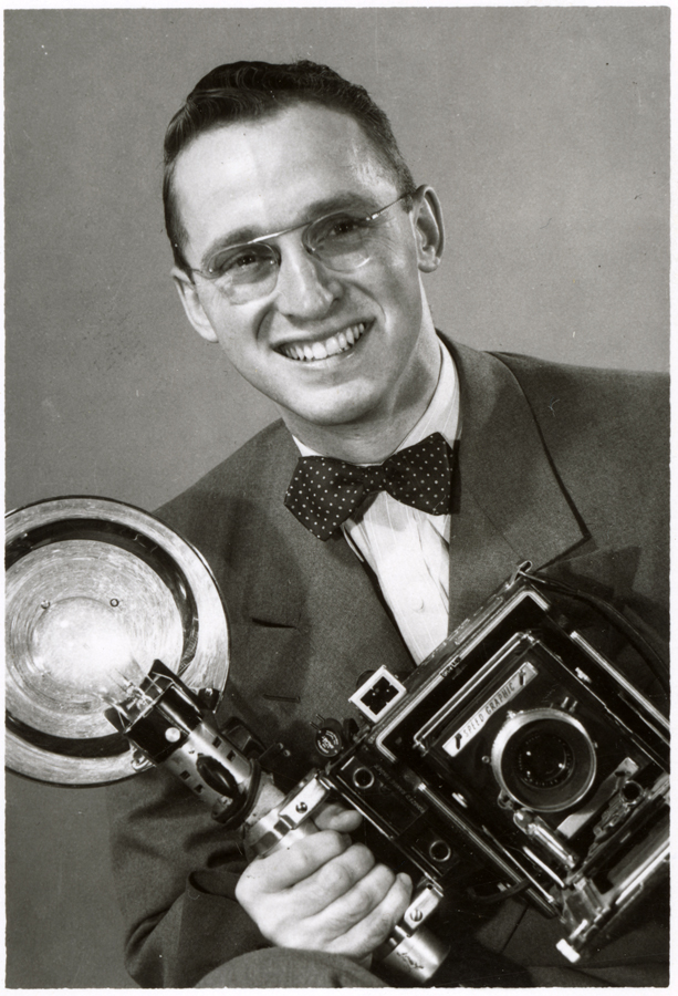 Russ Cooper poses with his Graflex Speed Graphic Camera, 1959