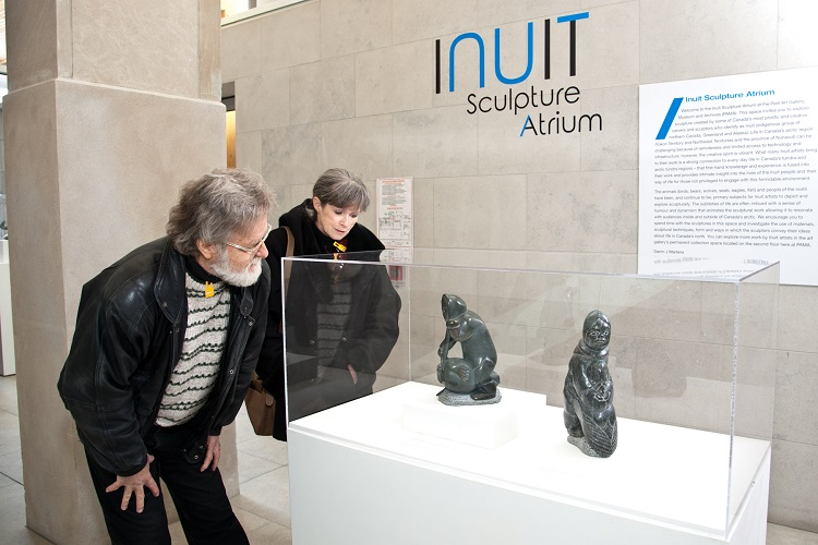 Guests exploring Inuit Sculpture Atrium in the main art gallery lobby